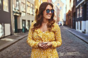 Smiling woman wearing sunglasses exploring city streets with her cellphone